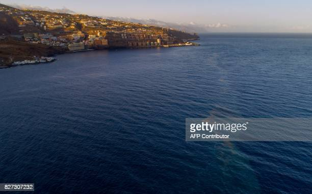 A picture taken with a drone shows a spot on the sea surface caused by microalgae near Tabaiba beach off the coast of El Rosario on August 5 2017 on...