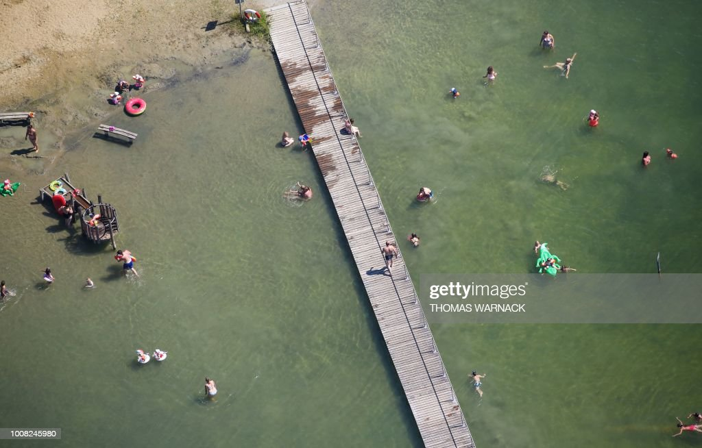 A Picture Taken With Drone Shows People On And Around Wooden Pier As They Are Taking Refreshing Bath In The Schwarzachtalsee Lake Ertingen