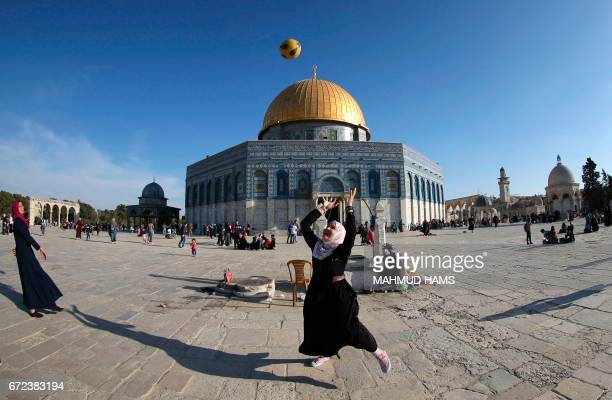 TOPSHOT A picture taken with a fisheye lens shows a Palestinian girl playing with a football at the AlAqsa Mosque compound during a ceremony...