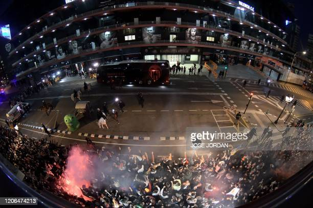 Picture taken with a fisheye lense shows the bus transporting Valencia´s player arriving at Mestalla´s stadium as supporters light flares in Valencia...