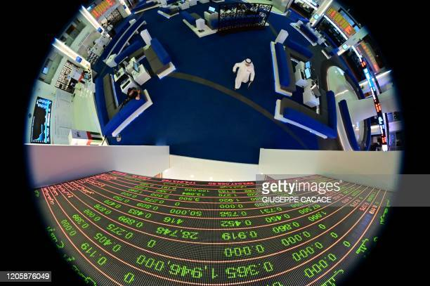 A picture taken with a fisheye lense shows traders walking by beneath a stock display board at the Dubai Stock Exchange in the United Arab Emirates...