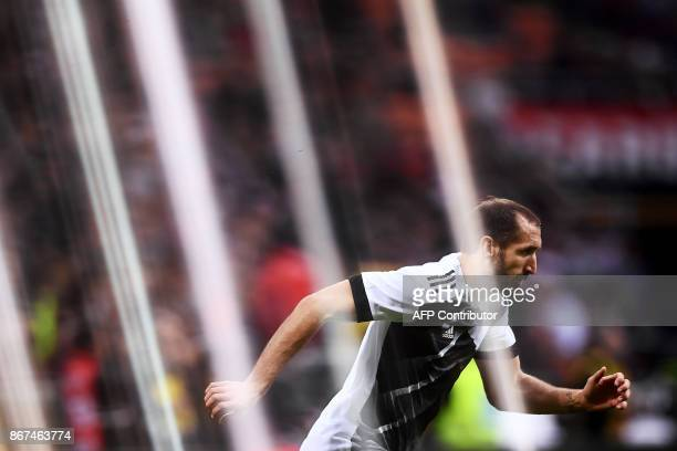 A picture taken with a gelatine filter shows Juventus' defender Giorgio Chiellini warming up before the Italian Serie A football match AC Milan Vs...