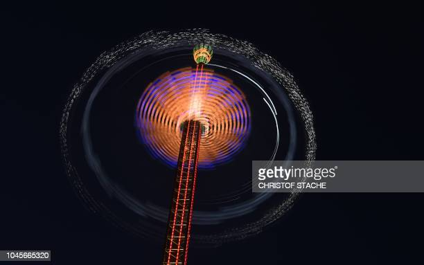 TOPSHOT Picture taken with a long time exposure shows a carousel at the Theresienwiese fairground of the Oktoberfest beer festival in Munich southern...