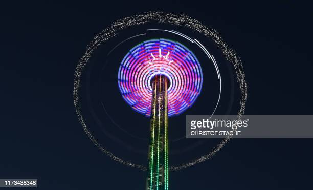 Picture taken with a long time exposure shows a carousel wheel at the Theresienwiese fairground of the Oktoberfest beer festival in Munich, southern...