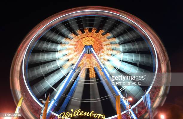 Picture taken with a long time exposure shows the ferris wheel at the Theresienwiese fairground of the Oktoberfest beer festival in Munich, southern...