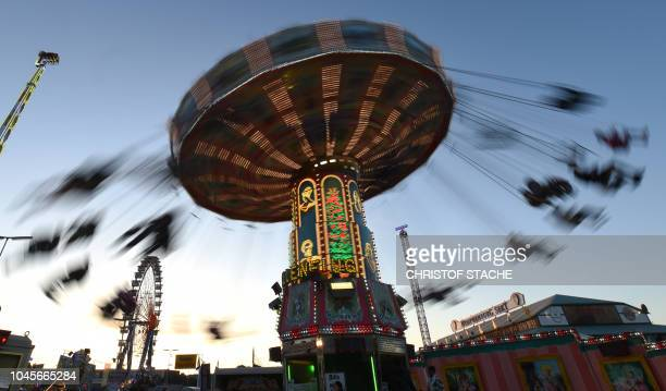 Picture taken with a long time exposure shows visitors sitting on a carousel at the Theresienwiese fairground of the Oktoberfest beer festival in...