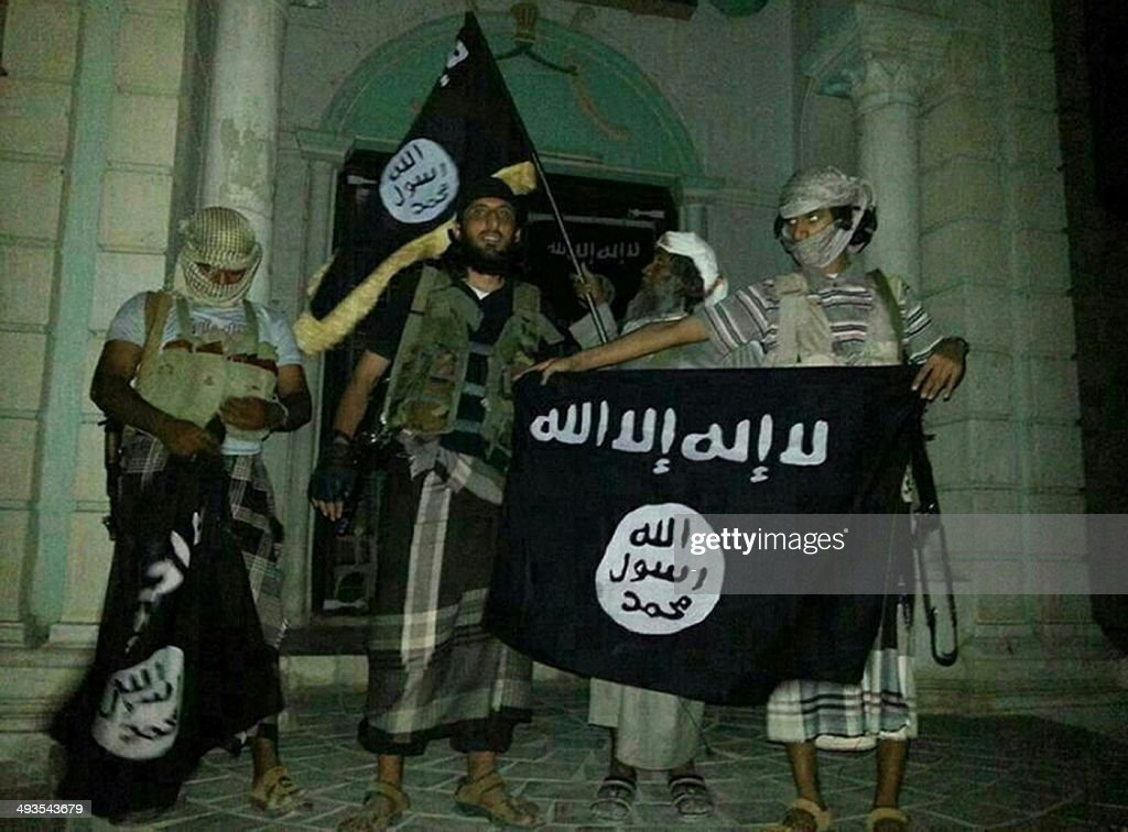 A picture taken with a mobile phone early on May 24, 2014 shows Al-Qaeda militants posing with Al-Qaeda flags in front of a museum in Seiyun, second Yemeni city of Hadramawt province, after launching a massive pre-dawn assault that killed at least 15 soldiers and police. The assault in Hadramawt, a jihadist stronghold that has seen large-scale attacks on the army in the past, came as troops pressed a month-old ground offensive against Al-Qaeda in Abyan and Shabwa provinces to the west.