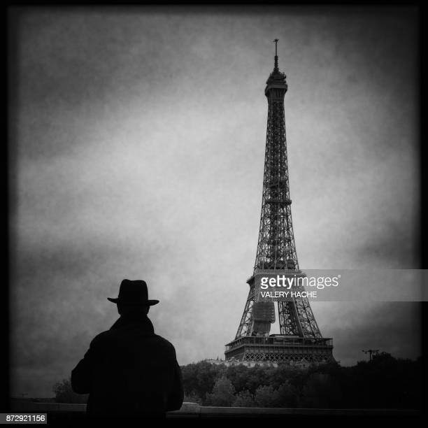 A picture taken with a mobile phone shows a man looking at the Eiffel Tower from a bridge across the Seine River in Paris on November 10 2017 / AFP...