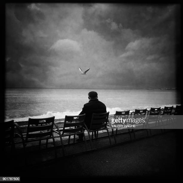 A picture taken with a mobile phone shows a man sitting on the 'Promenade des Anglais' on the French Riviera city of Nice on January 6 2018 / AFP...