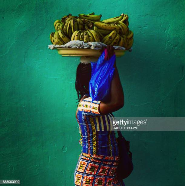 TOPSHOT A picture taken with a mobile phone shows a woman holding a tray of bananas in Libreville on the sidelines of the 2017 Africa Cup of Nations...
