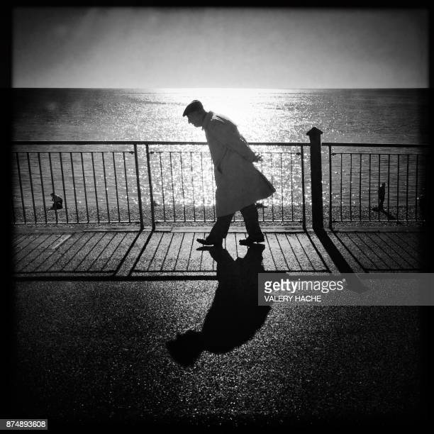 A picture taken with a mobile phone shows an elderly man walking along the 'Promenade des Anglais' in the French Riviera city of Nice on November 16...