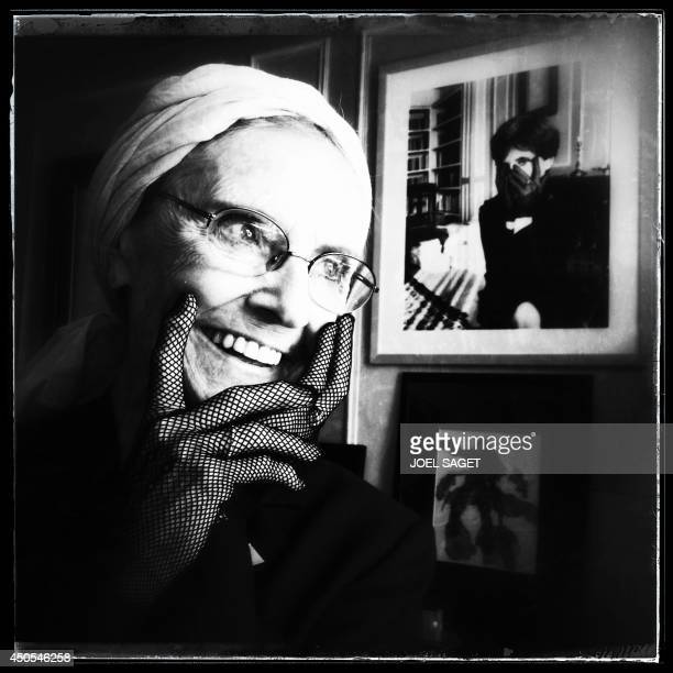 A picture taken with a mobile phone shows French writer Catherine RobbeGrillet posing at her home in NeuillysurSeine near Paris on June 12 2014 AFP...