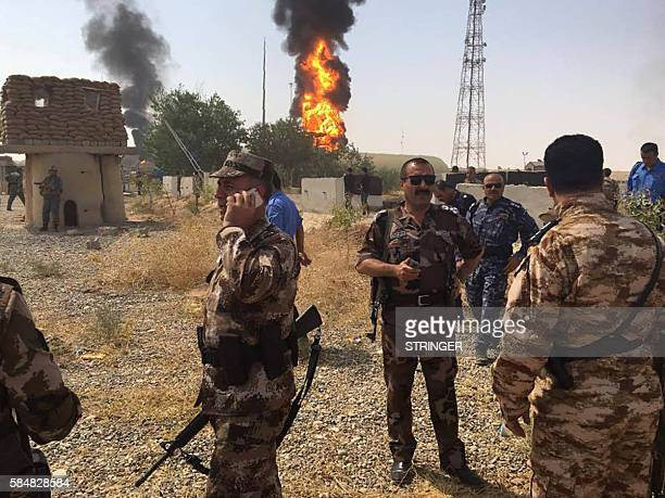 A picture taken with a mobile phone shows Peshmerga soldiers standing guard as smoke and flames billow from oil silos following an attack by...
