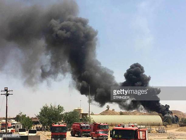 A picture taken with a mobile phone shows smoke billowing from oil silos following an attack by militants on a gas facility and the nearby Bai Hassan...