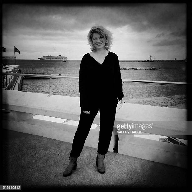 Picture taken with a mobile phone shows the French actress Cecile Bois posing for a photocall for a TV serie Candice Renoir during the MIPTV on April...