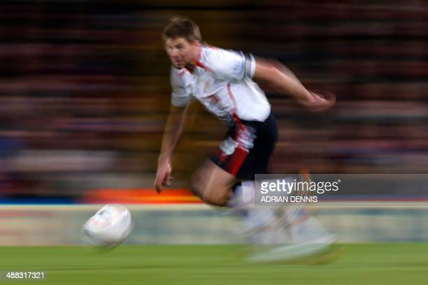 A picture taken with a slow shutter speed shows Liverpool's English midfielder Steven Gerrard on the ball during the English Premier League football...