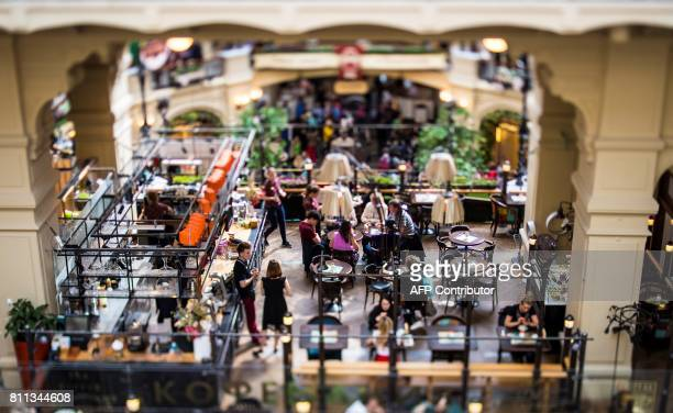 A picture taken with a tilt and shift lens shows people sitting at a cafe in the highend GUM shopping centre in Moscow on July 9 2017 / AFP PHOTO /...