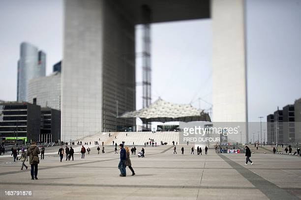 A picture taken with a tilt and shift lens shows people walking by the Grande Arche in the business district of La Defense outside Paris on March 15...