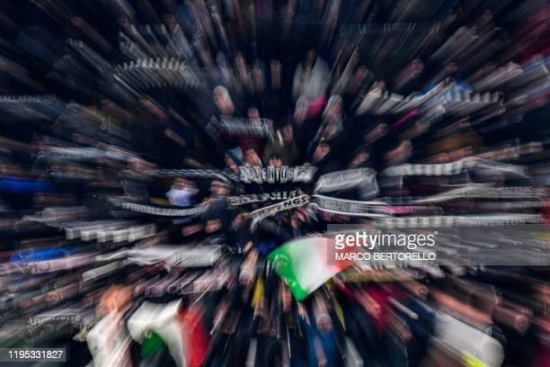 Picture taken with a zooming effect shows Juventus fans cheering during the Italian Cup round of 8 football match Juventus vs AS Roma on January 22,...