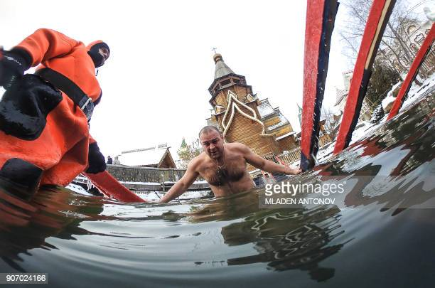 A picture taken with an action waterproof camera shows a diver supervising an Orthodox believer while he plunges in the icy waters of a pond during...