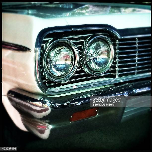A picture taken with an Hipstamatic application shows the headlight of a 1964 American Chevrolet Impala SS during a classic cars show at Saadabad...