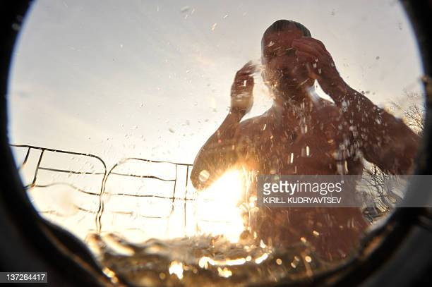 A picture taken with an underwater camera shows a Russian Orthodox church faithful gets out of the ice cold water of the Moskva River on January 18...