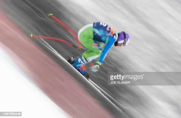 TOPSHOT Picture taken with long shutter speed shows Martin Cater of Slovenia racing down the hill during the third training of the men's downhill...
