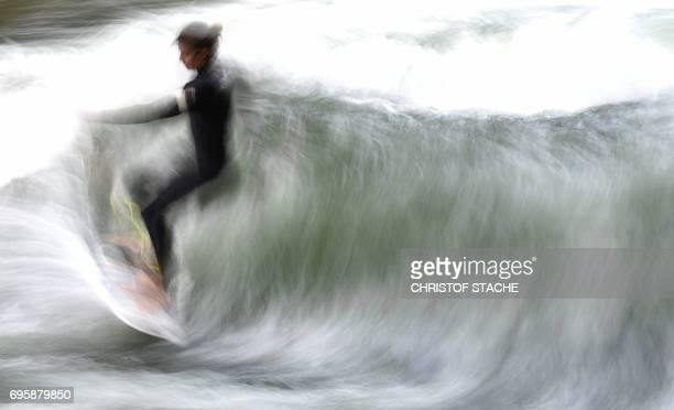 Picture taken with long time exposure shows a surfer riding on an artificial wave in the canal of the Eisbach river at the English Garden park in...