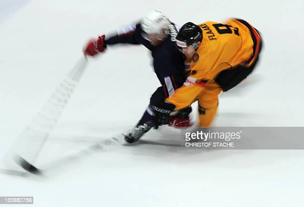 Picture taken with long time exposure shows German forward Jerome Flaake and US forward Sergio Somma challenging for the puck during the match...