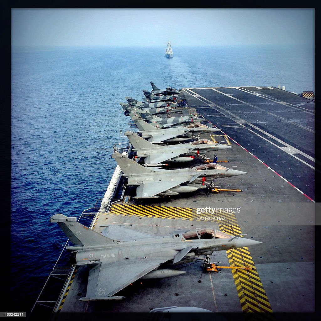 A picture taken with the Hipstamatic application shows French Navy fighter jets Rafale (foreground) and Super Etendards sitting on the flight deck of the aircraft carrier Charles de Gaulle escorted by the French Navy fregate Forbin while sailing in the Gulf of Oman on January 31, 2014.The Charles de Gaulle and the USS Harry S.Trumann (CVN 75) were conducting combined operations dubbed Bois Belleau.