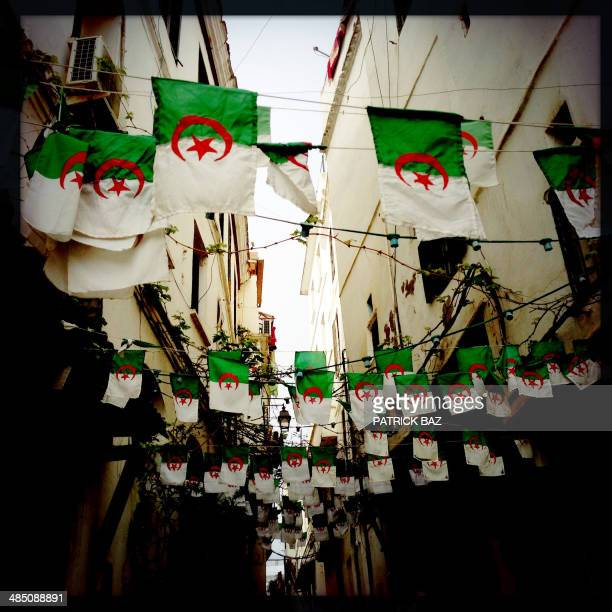 A picture taken with the Hipstamatic application shows rows of Algerian flags decorating a street in the old part of the capital Algiers known as the...