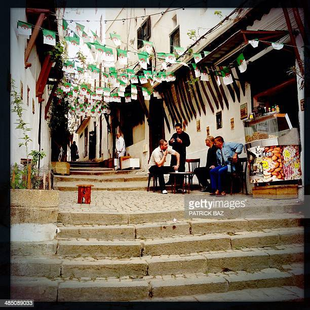 A picture taken with the Hipstamatic application shows rows of Algerian flags decorating a street as people sit around a table in the old part of the...