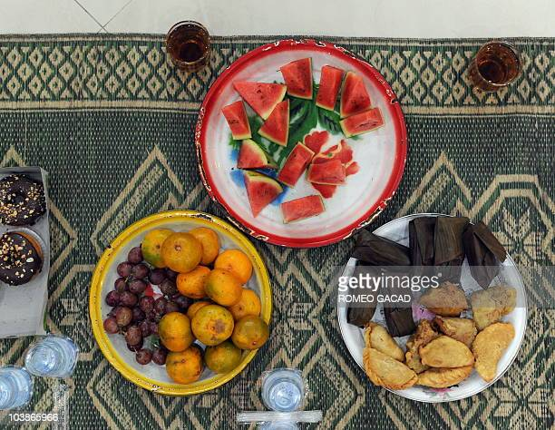 Pictured are dishes for Iftar a meal eaten to break the fast which consists of fruits rice cakes donuts tea and water that comes with gifts for the...