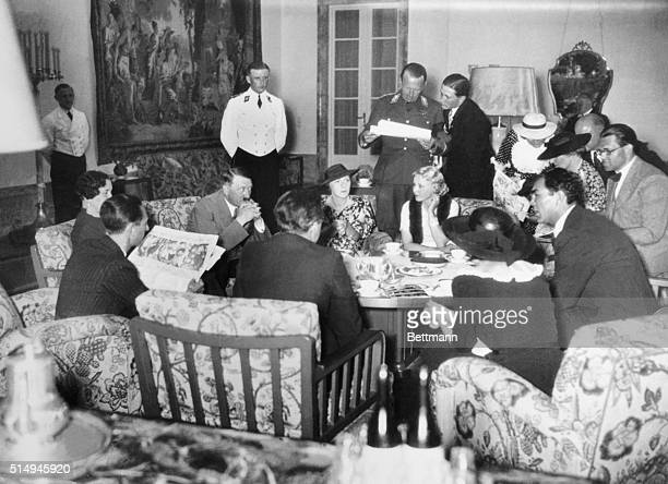 Pictured around a luncheon table in Chancellor Hitler's palace a group including the Dictator himself listens to Max Schmeling's story of how he...