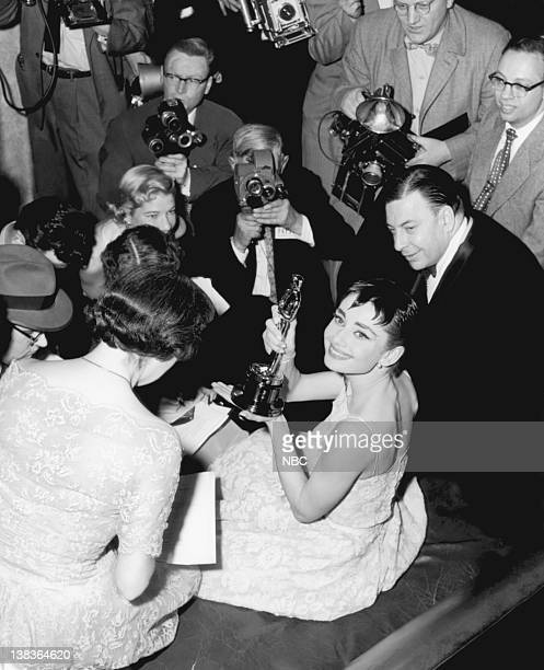 Audrey Hepburn wearing a Givenchy gown surrounded by journalists after winning her Best Actress Oscar at the ceremony in New York City