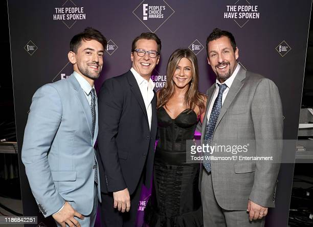 Pictured: Luis Gerardo Mendez, Sean Hayes, Jennifer Aniston and Adam Sandler pose backstage during the 2019 E! People's Choice Awards held at the...