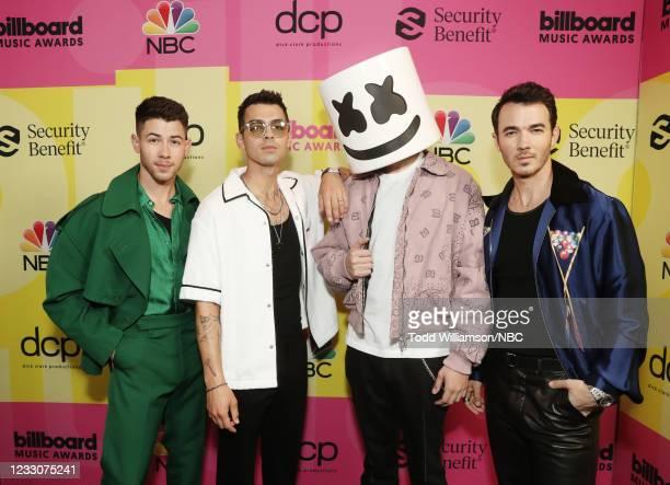 Pictured: Nick Jonas and Joe Jonas of Jonas Brothers, Marshmello, and Kevin Jonas of Jonas Brothers arrive to the 2021 Billboard Music Awards held at...