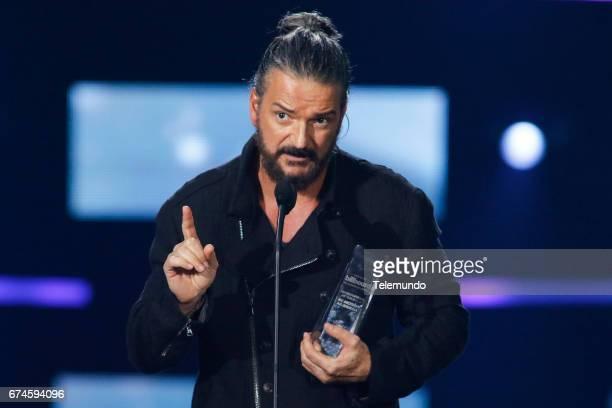 Ricardo Arjona accepts the 'Premio Billboard Trayectoria Artistica' award on stage at the Watsco Center in the University of Miami Coral Gables...