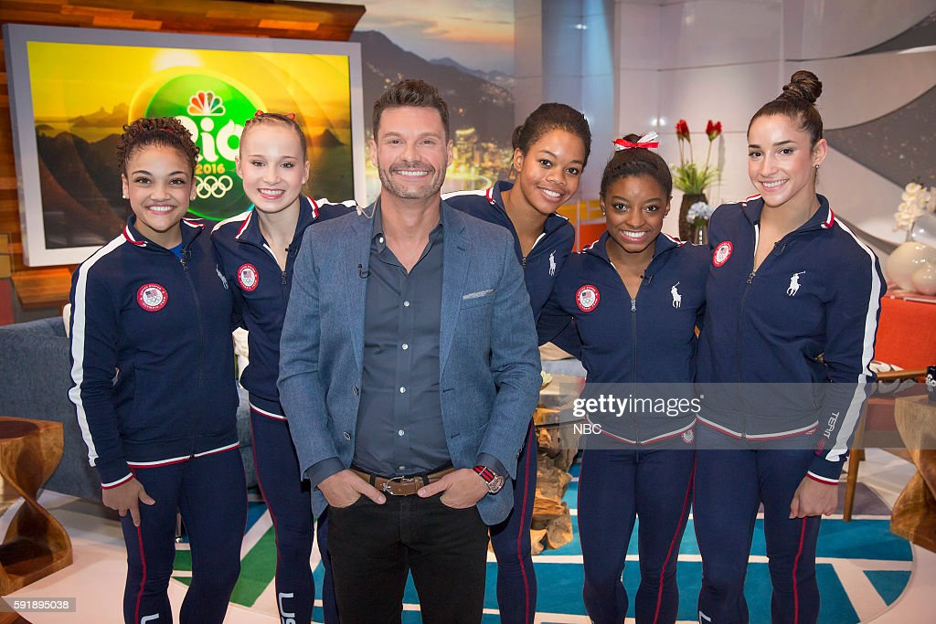 Ryan Seacrest (center) poses with U.S. Gymnasts (l-r) Laurie Hernandez, Madison Kocian, Gabby Douglas, Simone Biles, and Aly Raisman on August 4, 2016 --