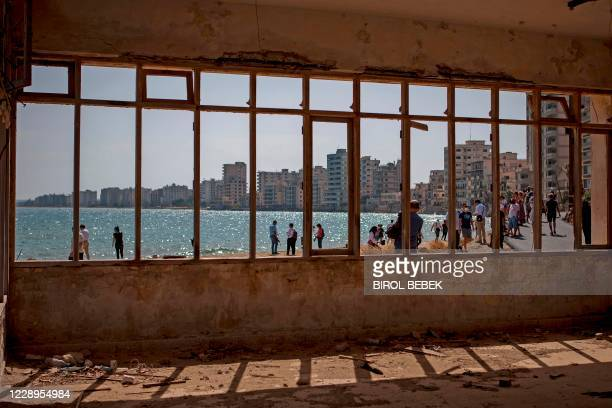 Pictured taken from inside an abandoned building shows people visiting Varosha, in the fenced off area of Famagusta, in the Turkish-occupied north of...