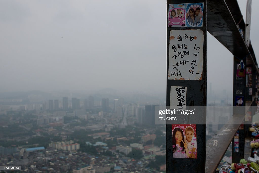 Pictures are stuck to a railing before the Seoul city skyline during rainfall on July 2, 2013. July marks the wet season for Seoul during which the city of10 million people receives some 60 percent of its annual rainfall. AFP PHOTO / Ed Jones