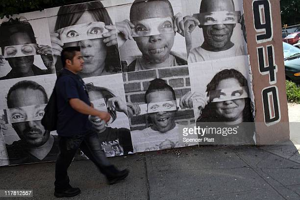 Pictures composed by the French street artist JR are plastered to a wall as part of a community project called 'Through A Mother's Eyes' which...