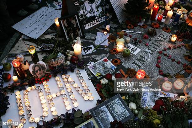 Pictures mementos and candles adorn Strawberry Fields in Central Park as people gather to commemorate the 25th anniversary of the death of John Lennon