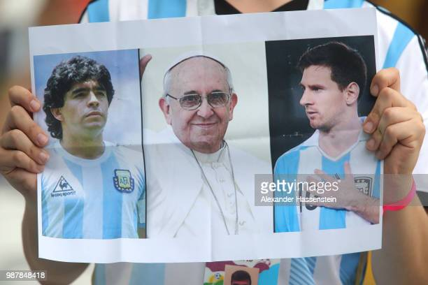 Pictures of Diego Armando Maradona Pope Francis anf Lionel Messi are shown by an Argentina fan prior to the 2018 FIFA World Cup Russia Round of 16...