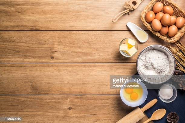 pictures of ingredients for making cakes bakery around, such as eggs, flour, sugar, butter, powder and equipment for making on a wooden floor, top view, with copy space. - table top shot stockfoto's en -beelden
