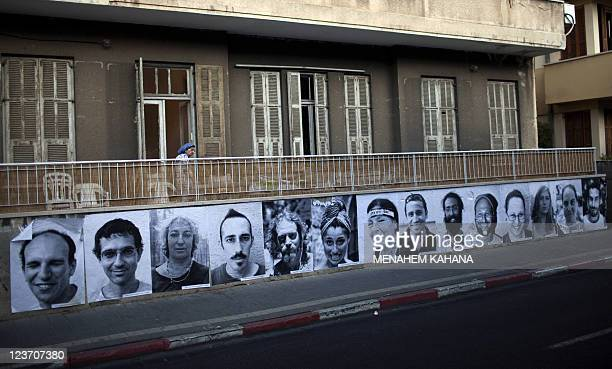 Pictures of Israelis taken by French street artist JR are plastered on a wall in Tel Aviv at the site of a tent camp set up to protest against rising...