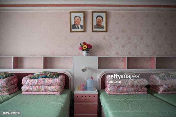 Pictures of Kim Ilsung and Kim Jongil hang over beds in accommodation quarters at the Kim Jong Suk Silk Factory on August 21 2018 in Pyongyang North...