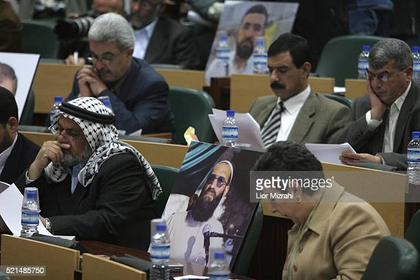 Pictures of lawmakers jailed in Israeli prisons sit among other parliamentarians as they listen to incoming Palestinian Prime Minister Ismail Haniyeh...