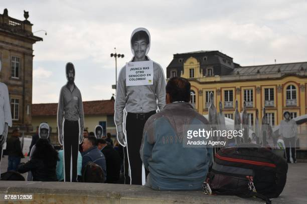 Pictures of missing people and victims of the armed conflict are displayed during a protest outside the Colon theater in Bogota as members of the...