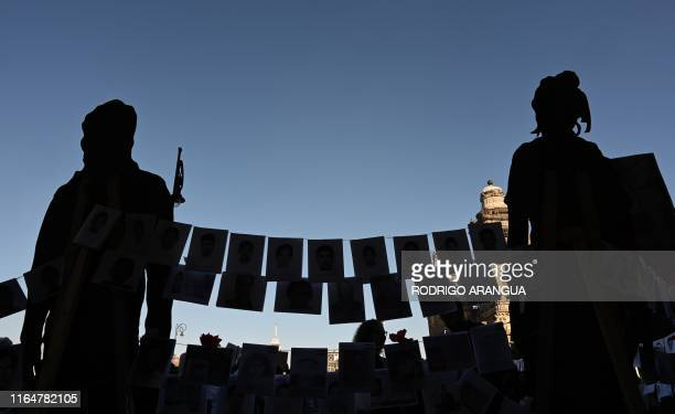 Pictures of missing persons hang from a rope in front of the National Palace during the commemoration of the International Day of the Disappeared in...